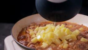 Het zetten van gehakte aardappel in de roux in pan met rundvlees stock videobeelden