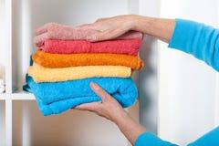 Het zetten van handdoeken op plank stock afbeelding