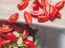Het zetten van heerlijke besnoeiingstomaten in de salade Royalty-vrije Stock Afbeeldingen