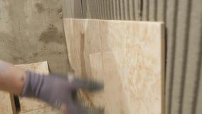 Het zetten van keramische tegel op de muur Ceramist legt langzaam keramische tegel op het hoogtepunt van de badkamersmuur van spe stock video