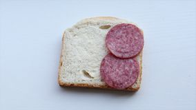 Het zetten van salami op brood stock footage
