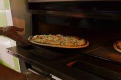 Het zetten van zeevruchtenpizza in oven stock foto