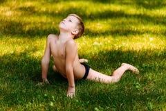 Het zeven-jaar-oude flexibele kind in zwembroek voert acrobatische oefeningen in de zomer op het groene gras uit royalty-vrije stock foto's