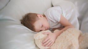 Het zeven-jaar-oude jongen dalende in slaap het koesteren stuk speelgoed draagt stock video