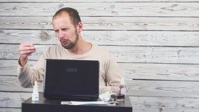 Het zieke Baardmens Hoesten, die bij werkplaats met computer zitten stock video