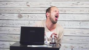 Het zieke Baardmens Hoesten, die bij werkplaats met computer zitten stock footage