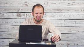 Het zieke Baardmens Hoesten, die bij werkplaats met computer zitten stock videobeelden