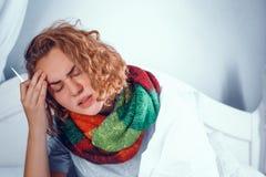 Het zieke blondemeisje is sjaal raakt haar hoofd In bed royalty-vrije stock fotografie