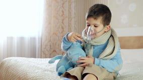 Het zieke kind ademt door verstuiver, thuis doet de baby inhalatie, jongen met een zuurstofmasker op zijn gezicht, behandeling stock videobeelden