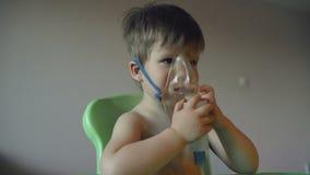Het zieke kind ademt thuis door verstuiversinhalatie, jongen met een zuurstofmasker op zijn gezicht die behandeling hebben stock video