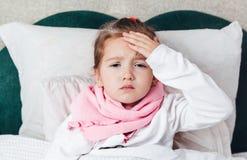 Het zieke kind die in het bed liggen en raakt haar forehaed Royalty-vrije Stock Foto