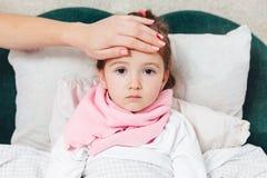 Het zieke kind die in het bed liggen en raakt haar forehaed Stock Fotografie