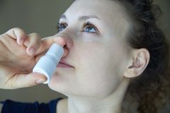Het zieke meisje bespuit de nevel van lopende neus in de neuspas royalty-vrije stock afbeeldingen