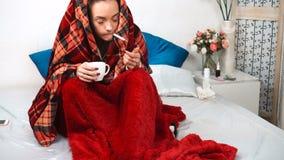 Het zieke meisje in deken vergt lichaamstemperatuur met termomentrom in bed stock footage