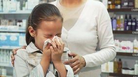 Het zieke meisje niest en veegt haar neus met een servet af stock video