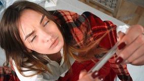 Het zieke meisje verpakte in deken en vergt lichaamstemperatuur met termomentrom stock video