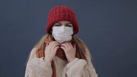 Het zieke meisje zet op een masker hoest en droevig stock video