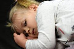 Het zieke meisjeskind ligt en is droevig stock foto