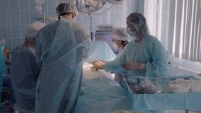 Het ziekenhuis chirurgisch team die chirurgie in werkende ruimte uitvoeren stock videobeelden