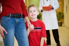 Het ziekenhuis: De glimlachende Jongen houdt de Hand van de Moeder vóór het Ontmoeten van Arts royalty-vrije stock foto's