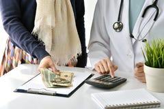 Het ziekenhuis en de medische uitgave, Arts en vrouw de patiënt berekenen op de prijslasten van de ziektebehandeling stock afbeelding