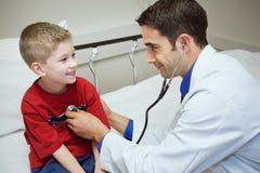 Het ziekenhuis: Het Hart van artsenlistens to boy ` s in Examenzaal royalty-vrije stock afbeelding