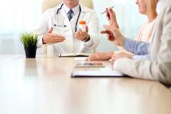 Het ziekenhuis, medisch onderwijs, gezondheidszorg, mensen en geneeskundeconcept - arts die meds aan de groep gelukkige artsen bi Stock Foto