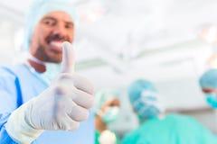 Het ziekenhuischirurgen die in verrichtingsruimte werken stock afbeeldingen