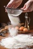 Het ziften van bloem met bloemfilter Het maken van koekjesa chef-kok die koekjes maken De eerste stap in het koken van bollen De  Royalty-vrije Stock Foto's