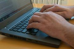 Het zijaanzicht over laptop op het bureau met mannelijke handen sluit omhoog Stock Afbeeldingen