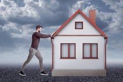 Het zijaanzicht van de jonge knappe mens in vrijetijdskleding het duwen één-storeyed losgemaakt huis op grintgrond met wolken stock afbeeldingen