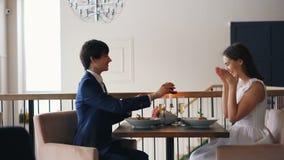 Het zijaanzicht van gelukkig paar in restaurant tijdens aanzoek, kerel spreekt en zet verlovingsring op meisje stock videobeelden
