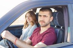 Het zijaanzicht van jong mooi paar heeft reis in auto, bekijkt camera, die in hun auto zijn, geniet van hoge snelheid Familiedekk stock foto's