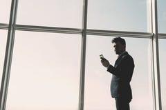 Het zijaanzicht van jonge zakenman bevindt zich dichtbij een panoramisch venster en bekijkt de telefoon stock fotografie
