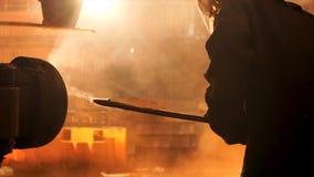 Het zijaanzicht van perator verwijdert afval uit ovenpijp bij de ijzer smeltende installatie Voorraadlengte Mensenarbeider in hit royalty-vrije stock afbeeldingen