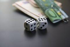 Het zijaanzicht van twee dobbelt en pakjes van geld Stock Fotografie