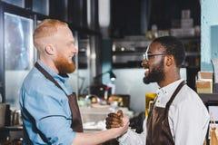 het zijaanzicht van twee jonge multi-etnische eigenaars van koffiewinkel in schorten het schudden dient koffie in stock fotografie