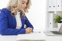 Het zijaanzicht van vrouw in blauwe blazer neemt nota's bij een lijst Stock Afbeeldingen