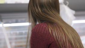 Het zijaanzicht van vrouw opent ijskast, zoekt naar bevroren voedsel in supermarkt stock videobeelden