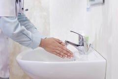 Het zijaanzicht van vrouwelijke arts die haar wassen dient de witte gootsteen met het stromende schuim van de waterzeep in de bad stock afbeelding
