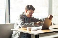 Het zijaanzichtportret van agressieve ongelukkige jonge zakenman in grijze blazer zit in koffie en hebbend slechte stemming zijn  royalty-vrije stock foto's