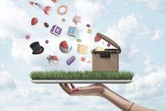 Het zijclose-up die van de hand van de vrouw digitale tablet met groen gras en vuilnisbak op het scherm houden en met misc heeft  royalty-vrije stock foto