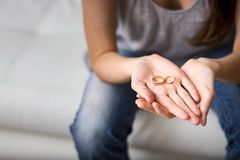 Het zijn droevige vrouw bekijkt de ring in de palm voor hem, nostalgisch over een vroegere echtgenoot, familie, huwelijk Het conc stock afbeeldingen