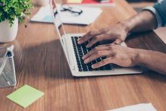 Het zijprofiel bebouwde foto van handen van de afro de Amerikaanse ` s zakenman op toetsenbord van laptop op een houten Desktop,  stock afbeeldingen