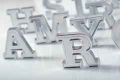 Het zilveren close-up van alfabetbrieven op een wit Royalty-vrije Stock Afbeeldingen