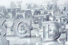 Het zilveren close-up van alfabetbrieven op een wit Stock Foto