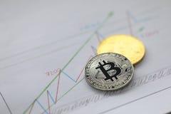 Het zilveren en gouden muntstuk van bitcoin ligt op zaken royalty-vrije stock afbeelding