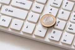 Het zilveren euro muntstuk met een verguld grensclose-up ligt op de sleutel met het aantal  Wit computertoetsenbord Aandeelhouder royalty-vrije stock afbeelding