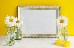 Het zilveren model van het kleurenkader met kamille bloeit in vazen op een gele achtergrond De ruimte van het exemplaar Stock Foto