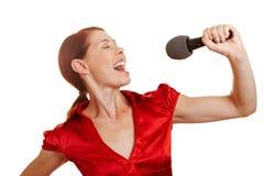 Het zingen van de vrouw met microfoon Stock Foto